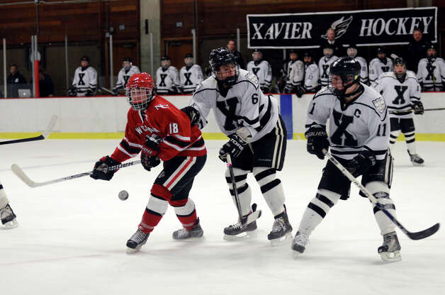 New Canaan's Peter Richardson (18) and Xavier's Evan Lindquist (6) go after the puck during the boys hockey game at the Freeman Athletic Center in Middletown on Monday, Jan. 21, 2013. Photo: Amy Mortensen / Connecticut Post Freelance