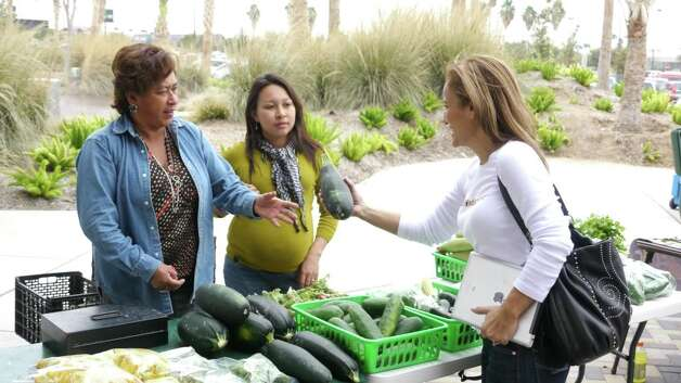 Vendors at the McAllen Farmers Market talk business with a customer. Photo: San Antonio Express-News