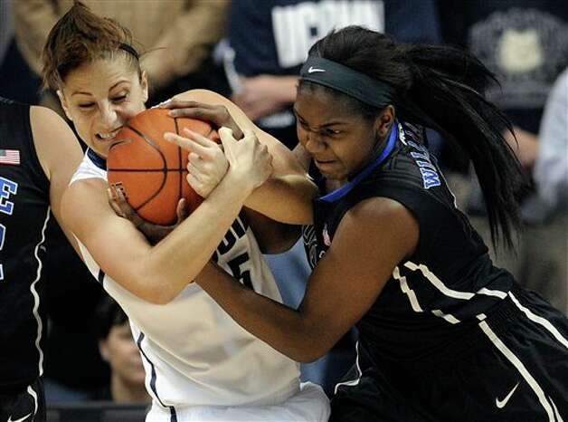 UConn's Caroline Doty and Duke's Elizabeth Williams, right, scrap for the ball during the first half of an NCAA college basketball game in Storrs, Conn., Monday, Jan. 21, 2013. (AP Photo/Jessica Hill)