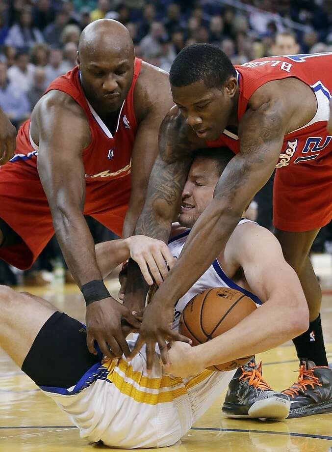 Golden State Warriors' David Lee, center, tries to keep a loose ball from Los Angeles Clippers' Lamar Odom, left, and Eric Bledsoe during the first half of an NBA basketball game in Oakland, Calif., Monday, Jan. 21, 2013. (AP Photo/Marcio Jose Sanchez) Photo: Marcio Jose Sanchez, Associated Press