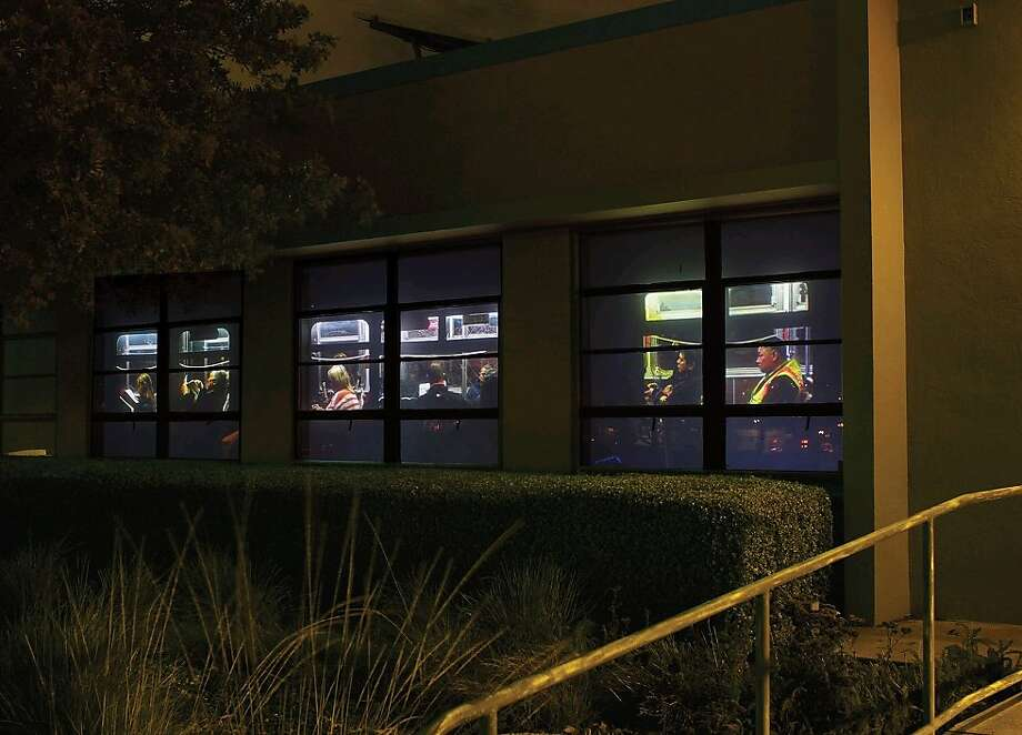 "Recology artist in residence Michael Damm's ""Incidental Films for an Accidental Audience: On Tunnel"" (2013), is a video installation using bus imagery projected onto a series of windows at a building on Tunnel Avenue in S.F. Photo: Recology"