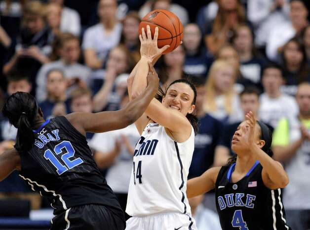 Connecticut's Kelly Faris, center, is pressured by Duke's Chelsea Gray, left, and Chloe Wells, right, during the first half of an NCAA college basketball game in Storrs, Conn., Monday, Jan. 21, 2013. (AP Photo/Jessica Hill) Photo: Jessica Hill, Associated Press / FR125654 AP