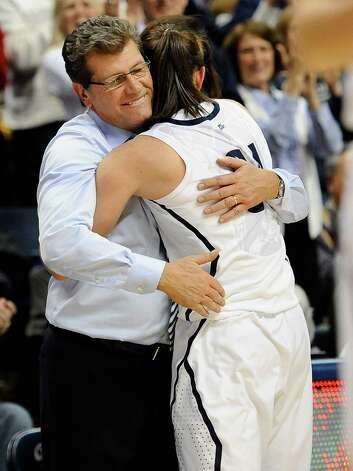 Connecticut coach Geno Auriemma, left, hugs Connecticut's Kelly Faris during the second half of an NCAA college basketball game in Storrs, Conn., Monday, Jan. 21, 2013. Faris had 18 points and 12 rebounds in Connecticut's 79-49 win over Duke. (AP Photo/Jessica Hill) Photo: Jessica Hill, Associated Press / FR125654 AP