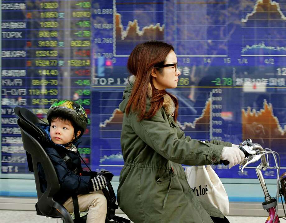 A mother and child cycle past an electronic stock board of a securities firm in Tokyo, Monday, Jan. 21, 2013. Asian stock markets were mixed Monday amid uncertainty about the outcome of a central bank meeting in Japan and nervousness over whether U.S. political leaders will be able to reach a deal on the government's debt limit.  (AP Photo/Koji Sasahara) Photo: Koji Sasahara, STF / AP