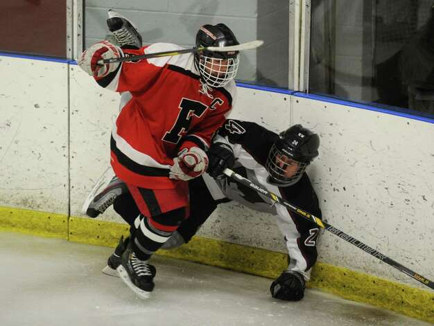 Fairfield's Mike Aquila checks Milford's Jarrod Butts into the boards during the second period of their boys hockey matchup at the Milford Ice Pavilion on Monday, January 21, 2013. Photo: Brian A. Pounds