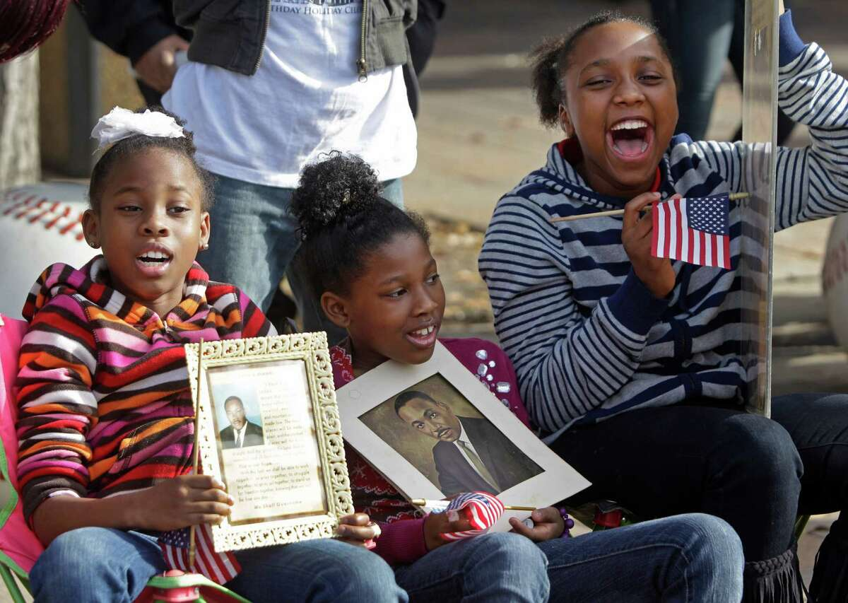 """Cayle Owens, 8, left, and her sisters, Cierra Owens, 9, center, and Daniello Owens, 10, pay homage to Martin Luther King Jr., while watching the Black Heritage Society's """"Original"""" MLK parade in downtown Houston."""