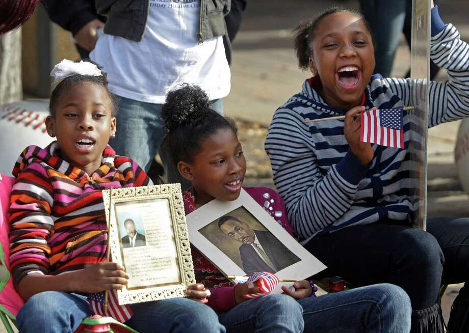 "Cayle Owens, 8, left, and her sisters, Cierra Owens, 9, center, and Daniello Owens, 10, pay homage to Martin Luther King Jr., while watching the Black Heritage Society's ""Original"" MLK parade in downtown Houston. Photo: Melissa Phillip, Staff / © 2013 Houston Chronicle"