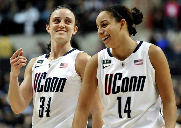 Connecticut's Kelly Faris (34) and Connecticut's Bria Hartley (14) smile during the second half of an NCAA college basketball game against Duke in Storrs, Conn., Monday, Jan. 21, 2013. Connecticut won 79-49. (AP Photo/Jessica Hill) Photo: Jessica Hill, Associated Press / FR125654 AP