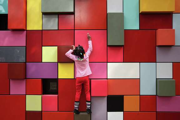 "Kabriel Green, 5, climbs the ""art boxes"" or the public art called the Synchronicity of Color by  Margo Sawyer at Discovery Green on Matin Luther King Day on Monday, Jan. 21, 2013, in Houston."