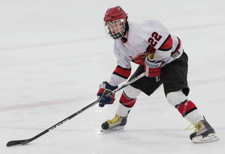 Greenwich high school's Decker Curran looks to pass to a teammate in a boys ice hockey game against