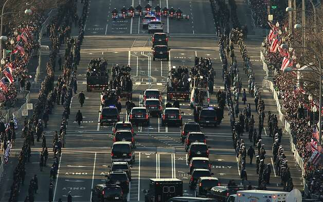 Hundreds of thousands line the streets as the presidential motorcade makes its way down the inaugural parade route. Photo: Molly Riley/AFP, McClatchy-Tribune News Service