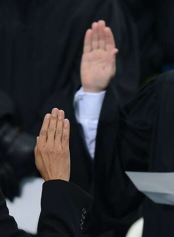 US President Barack Obama (bottom hand) takes the oath of office during the 57th Presidential Inauguration ceremonial swearing-in at the US Capitol on January 21, 2013 in Washington, DC. The oath was administered by US Supreme Court Chief Justice John Roberts, Jr.   AFP PHOTO / Saul LOEBSAUL LOEB/AFP/Getty Images Photo: Saul Loeb, AFP/Getty Images