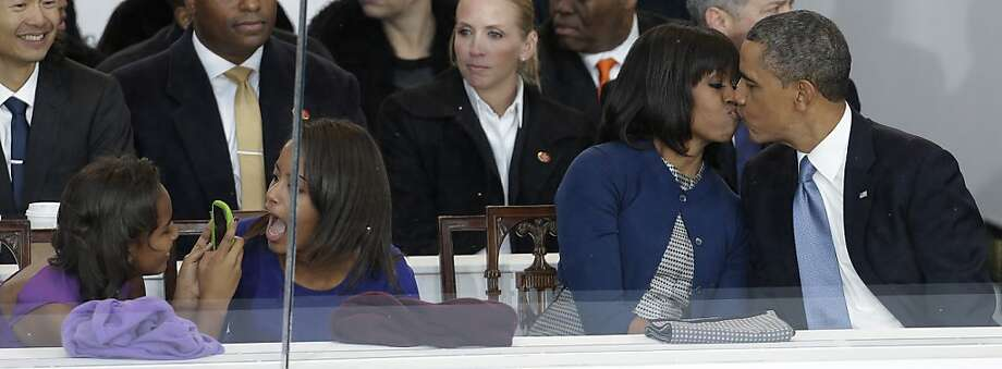 President Barack Obama kisses first lady Michelle Obama as their daughters Sasha, left, and Malia, second from left, look on during the Inaugural parade, Monday, Jan. 21, 2013, in Washington. Thousands  marched during the 57th Presidential Inauguration parade after the ceremonial swearing-in of President Barack Obama. (AP Photo/Gerald Herbert) Photo: Gerald Herbert, Associated Press