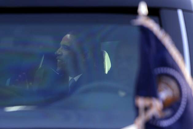 President Barack Obama is seen waving from inside his limousine as he and first lady Michelle Obama drive in the inaugural parade during the 57th Presidential Inauguration in Washington, Monday, Jan. 21, 2013. (AP Photo/Charles Dharapak) Photo: Charles Dharapak, Associated Press