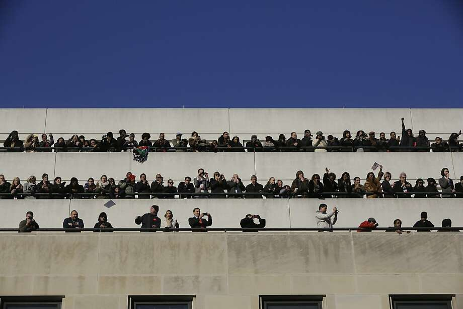 Spectators on top of buildings watch as President Barack Obama and first lady Michelle Obama participate in the parade during the 57th Presidential Inauguration in Washington, Monday, Jan. 21, 2013. (AP Photo/Charles Dharapak) Photo: Charles Dharapak, Associated Press