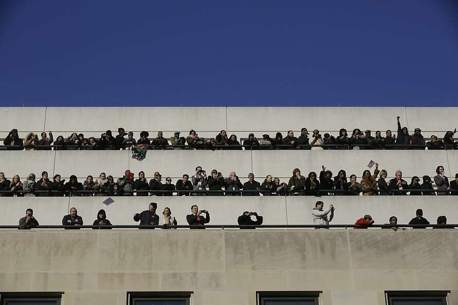 Spectators on top of buildings watch as President Barack Obama and first lady Michelle Obama partici