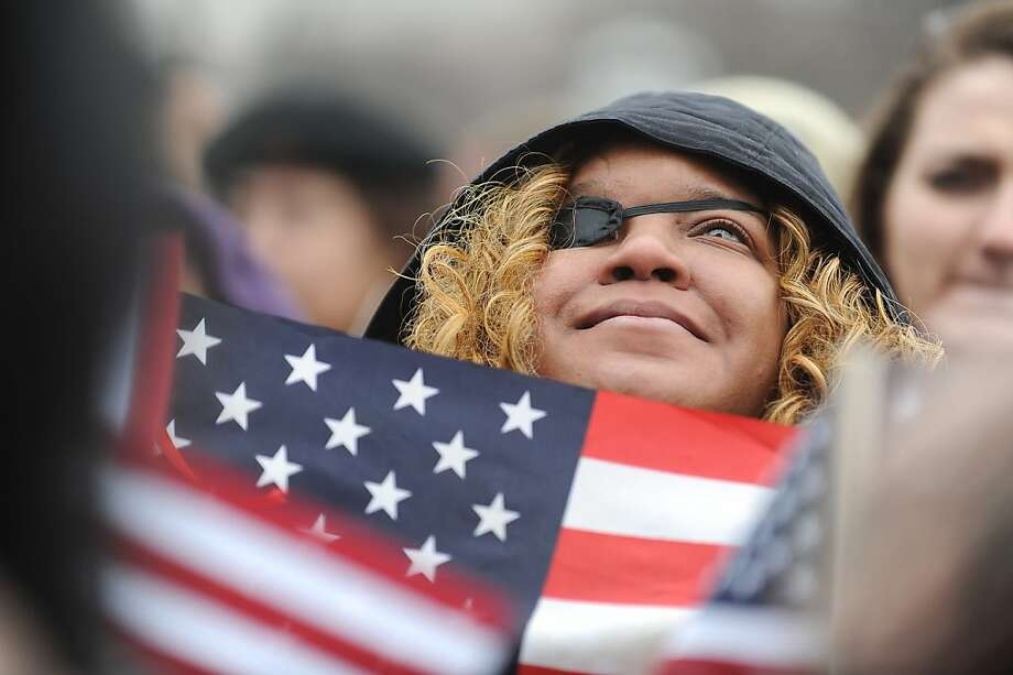 Tara Raigns, 32, of Petersburg, Virginia, stands on the National Mall and listens to President Barack Obama make remarks and take the oath of office, Monday, January 21, 2013. (Mary F. Calvert/MCT) Photo: Mary F. Calvert, McClatchy-Tribune News Service