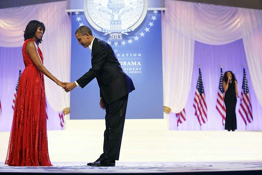 President Barack Obama bows as he and first lady Michelle Obama, wearing a ruby colored chiffon and