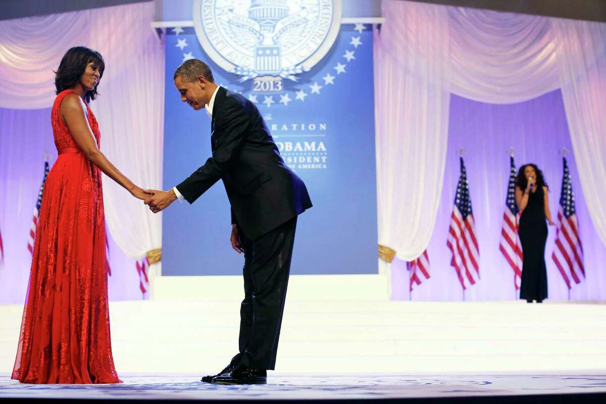 President Barack Obama bows as he and first lady Michelle Obama, wearing a ruby colored chiffon and velvet Jason Wu gown, gets ready to dance as singer Jennifer Hudson, right, sings Al Green's