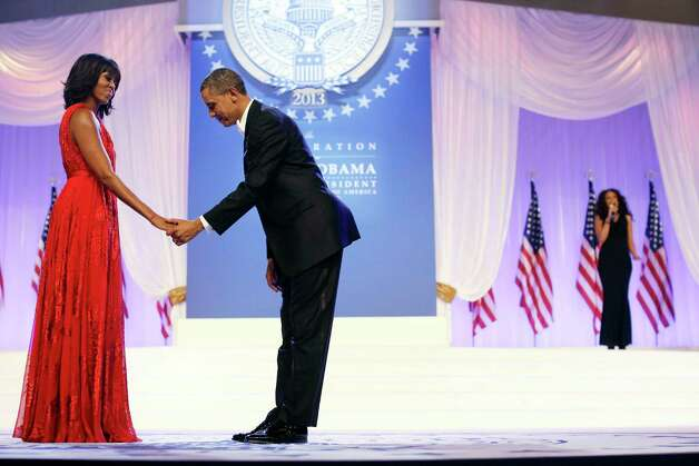 "President Barack Obama bows as he and first lady Michelle Obama, wearing a ruby colored chiffon and velvet Jason Wu gown, gets ready to dance as singer Jennifer Hudson, right, sings Al Green's ""Let's Stay Together"" at the Inaugural Ball at the Washington Convention Center in Washington during the 57th Presidential Inauguration, Monday, Jan. 21, 2013. Photo: AP"