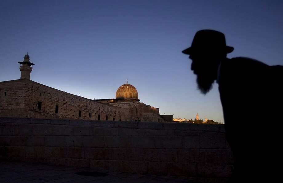 An Ultra Orthodox Jewish man walks in front of  the Al Aqsa Mosque, background, in Jerusalem's old city, Monday, Jan. 21, 2013. General elections in Israel will be held on Tuesday, Jan. 22. Photo: Sebastian Scheiner, Associated Press