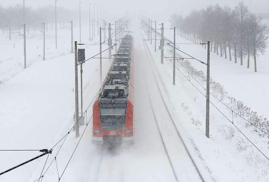 A regional train drives on a snow covered track heading to the Franz-Josef-Strauss airport in Munich, southern Germany, during a heavy snowfall on January 21, 2013. Photo: Christof Stache, AFP/Getty Images