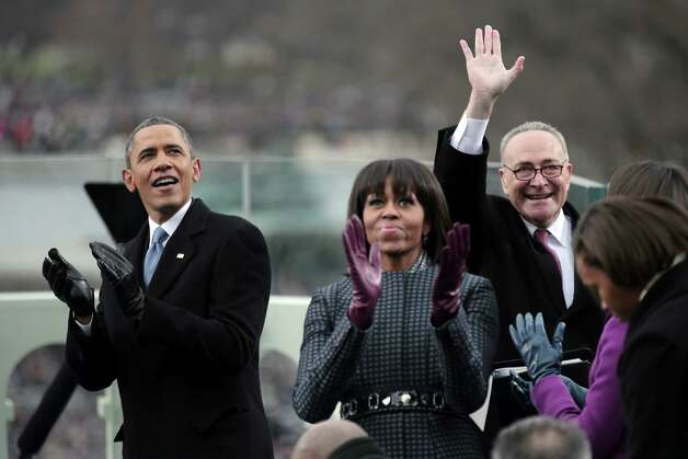 President Barack Obama and first lady Michelle Obama applaud, as Sen. Charles Schumer, D-N.Y., chairman of the Joint Congressional Committee on Inaugural Ceremonies waves on the West Front of the Capitol in Washington, Monday, Jan. 21, 2013, prior to Obama's ceremonial swearing-in ceremony during the 57th Presidential Inauguration.  (AP Photo/Win McNamee, Pool) Photo: Win McNamee