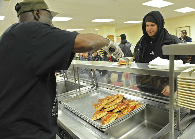 Pizza donated by Domino's is given out to a large amount of homeless people during snack time at the Capitol City Rescue Mission on Monday Jan. 21, 2013 in Albany, N.Y. The larger than normal number of people is due to freezing temperatures outside. (Lori Van Buren / Times Union) Photo: Lori Van Buren