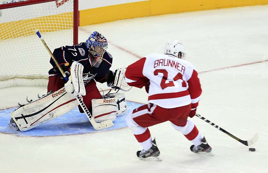 Detroit rookie Damien Brunner (right) positions himself against Columbus goalie Sergei Bobrovsky for the game-winning goal in the fourth round of a shootout. Photo: Jay LaPrete, Associated Press