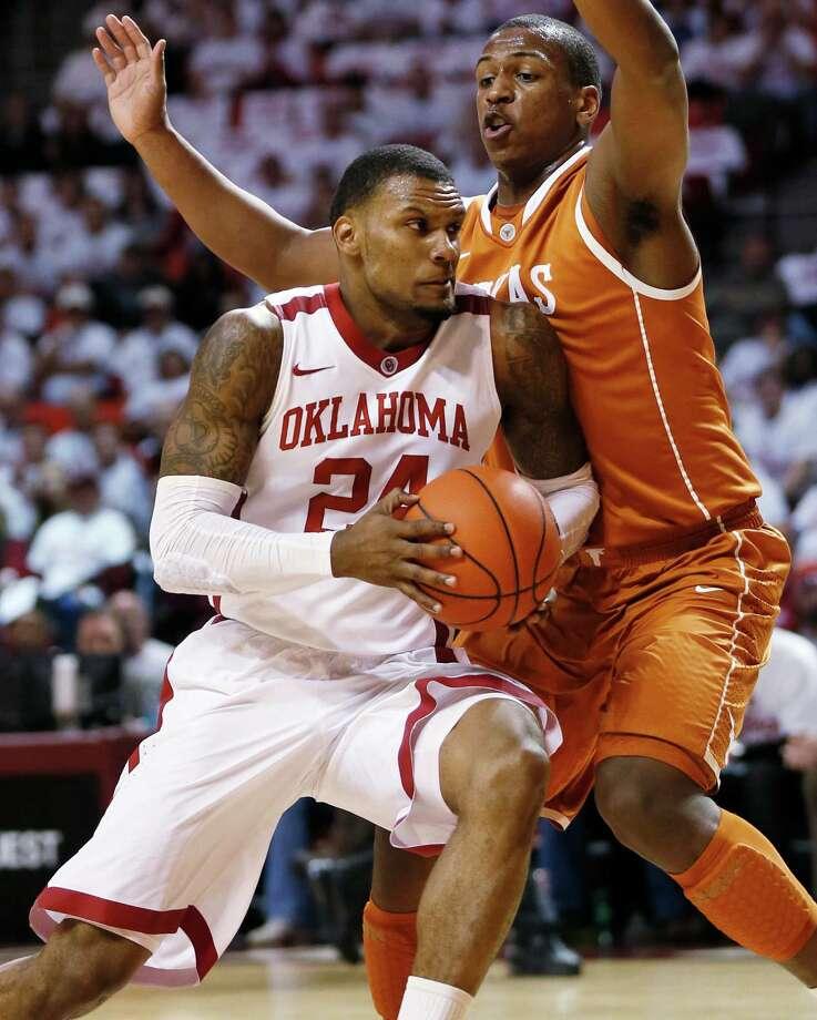 Oklahoma's Romero Osby (24) drives to the basket against Texas' Jonathan Holmes (10) during an NCAA college basketball game in Norman, Okla., Monday, Jan. 21, 2013. (AP Photo/The Oklahoman, Nate Billings) Photo: Nate Billings, MBI / The Oklahoman