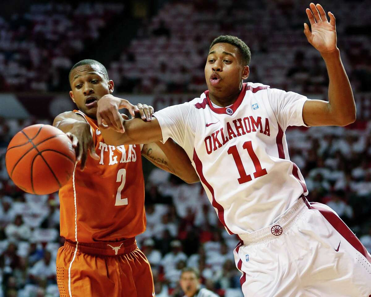 Texas' Demarcus Holland (2) knocks the ball away from Oklahoma's Isaiah Cousins (11) during an NCAA college basketball game in Norman, Okla., Monday, Jan. 21, 2013. (AP Photo/The Oklahoman, Nate Billings)