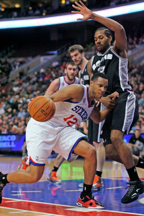 The Spurs' Kawhi Leonard defends as Philadelphia 76ers' Evan Turner (12) drives into the lane in the first half Monday, Jan. 21, 2013, in Philadelphia. Photo: H. Rumph Jr, Associated Press / FR61717 AP