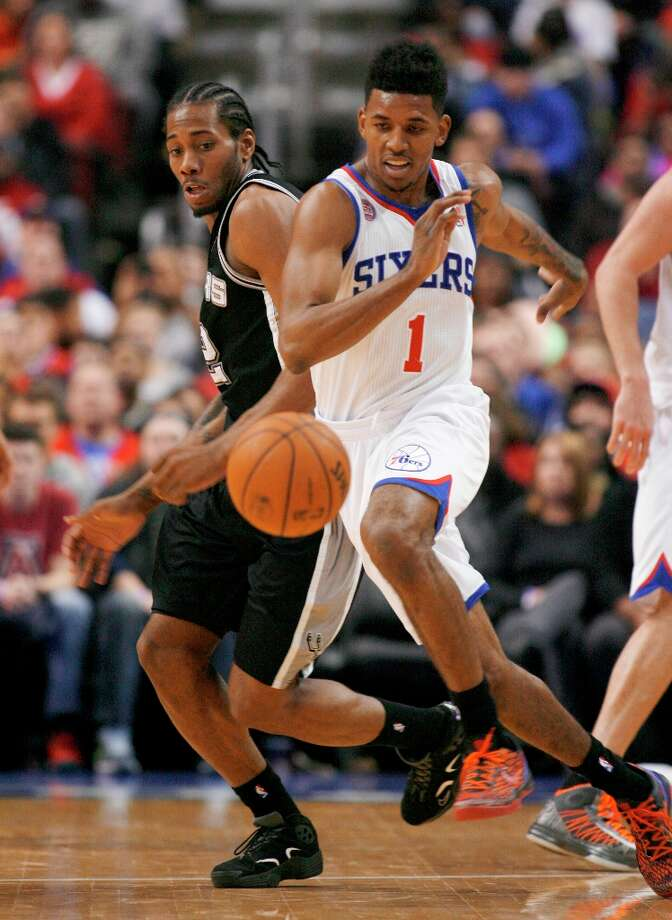 The Spurs' Kawhi Leonard (2) and Philadelphia 76ers' Nick Young (1) chase a loose ball in the second half  Monday Jan. 21, 2013, in Philadelphia. The Spurs won 90-85. Photo: H. RUMPH JR, Associated Press / FR61717 AP
