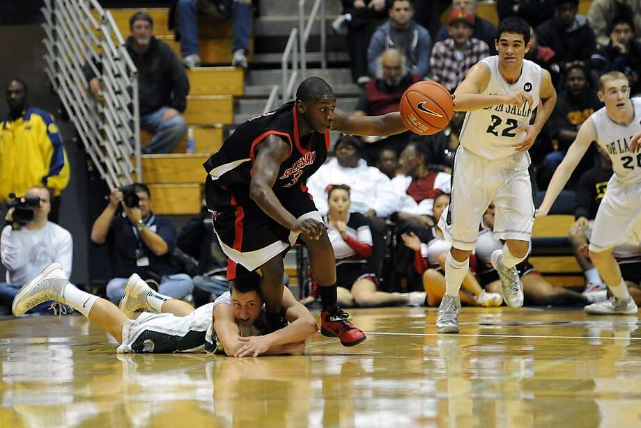 Salesian's Mario Dunn has the ball and De La Salle's Michael Inman has the ankle in Salesian's win at Cal. Photo: Michael Short, Special To The Chronicle