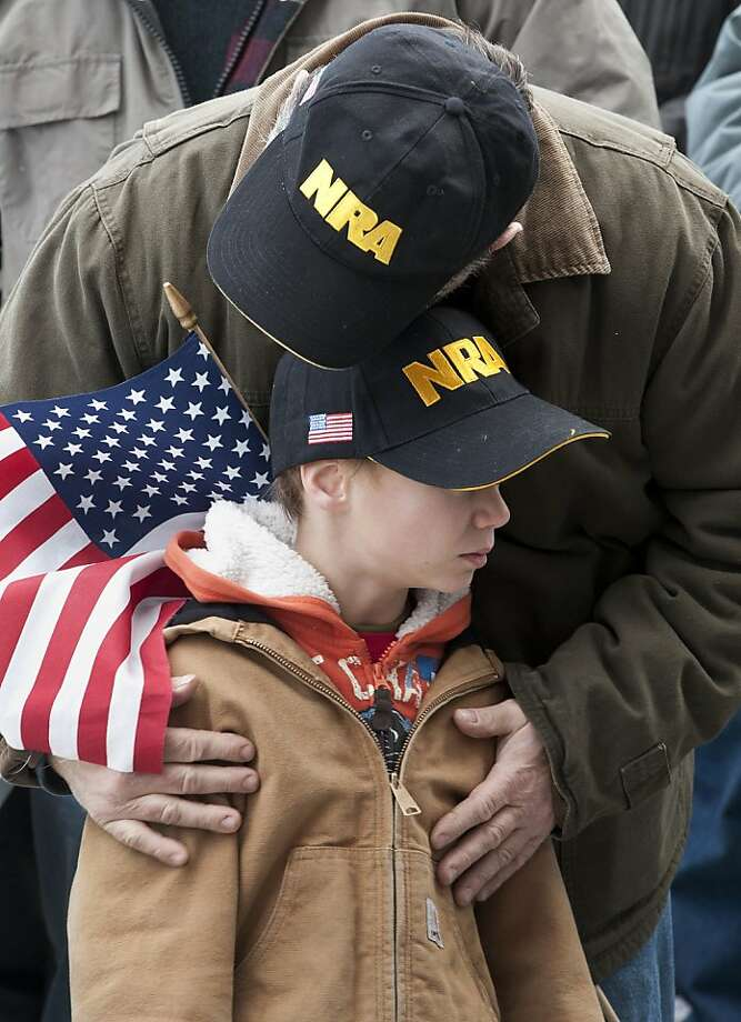 "Gun rights supporter Kenny Deal of Stafford, Conn., hugs his son Daniel, at rally at the Capitol in Hartford, Conn., Saturday, Jan. 19, 2013.  The rally, dubbed, ""Guns Across America"", at Connecticut's state Capitol and state capitol buildings across the country to raise concerns about possible new gun legislation that could affect gun owners' rights in the wake of the Dec. 14 school shooting at Sandy Hook Elementary School in Newtown. Photo: Jessica Hill, Associated Press"