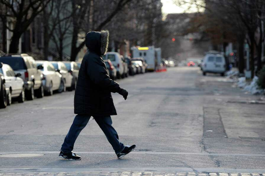 A person is bundled up against wind and cold on State Street on Tuesday, Jan. 22, 2013,  in Albany,