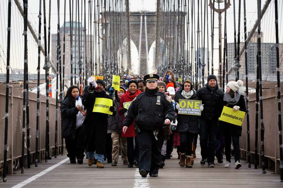 A NYPD officer leads demonstrators over the Brooklyn bridge towards downtown Manhattan during a One Million Moms for Gun Control Rally, Jan. 21, 2012, in New York. Demonstrators called for new gun control legislation, demanding a ban on assault weapons and stricter regulations on gun purchases. The One Million Moms for Gun Control group formed in the wake of last month's massacre at a Connecticut elementary school. Photo: John Minchillo, AP / FR170537 AP