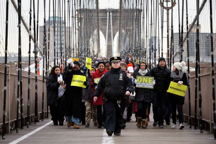 A NYPD officer leads demonstrators over the Brooklyn bridge towards downtown Manhattan during a One