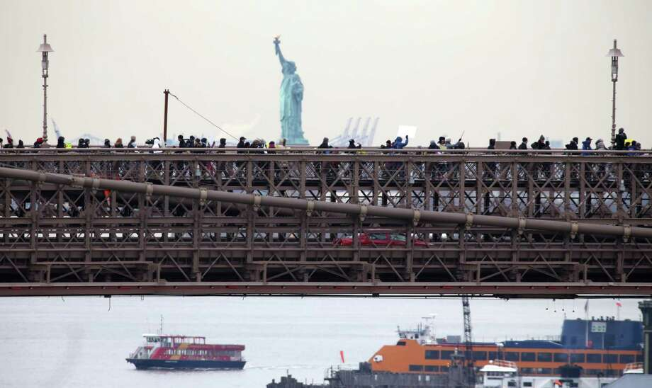 People organized by a gun control group formed in the wake of last month's massacre at a Connecticut elementary school march across the Brooklyn Bridge on Monday, Jan. 21, 2013, in New York. Organizers One Million Moms for Gun Control wants Congress to follow New York's lead and enact stricter limits on weapons and ammunition purchases. Photo: Peter Morgan, AP / AP