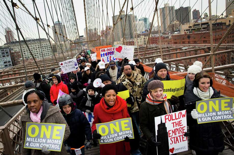 Demonstrators march over the Brooklyn bridge towards downtown Manhattan during the One Million Moms for Gun Control Rally, Jan. 21, 2012, in New York. Demonstrators called for new gun control legislation, demanding a ban on assault weapons and stricter regulations on gun purchases. The One Million Moms for Gun Control group formed in the wake of last month's massacre at a Connecticut elementary school. Photo: John Minchillo, AP / FR170537 AP