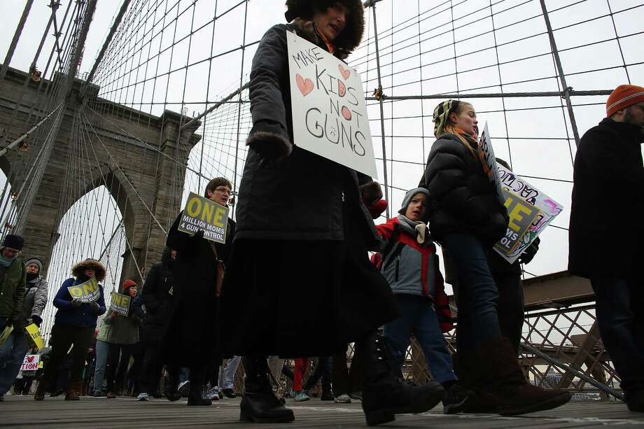 NEW YORK, NY - JANUARY 21:  Participants with One Million Moms for Gun Control, a gun control group formed in the wake of last month's massacre at a Newtown, Connecticut elementary school, attend a rally and march across the Brooklyn Bridge on January 21, 2013 in New York City.  The group marched to City Hall where they held a rally and demanded stricter measures against guns. One Million Moms for Gun Control said the event is inspired by the Rev. Martin Luther King Jr.'s message of nonviolence. Photo: Spencer Platt, Getty Images / 2013 Getty Images