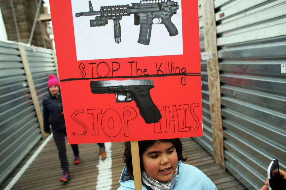 NEW YORK, NY - JANUARY 21:  Luna Miller holds a anti gun sign while participating in a rally and march across the Brooklyn Bridge with One Million Moms for Gun Control, a gun control group formed in the wake of last month's massacre at a Newtown, Connecticut elementary school on January 21, 2013 in New York City. The group marched to City Hall where they held a rally and demanded stricter measures against guns. One Million Moms for Gun Control said the event is inspired by the Rev. Martin Luther King Jr.'s message of nonviolence. Photo: Spencer Platt, Getty Images / 2013 Getty Images