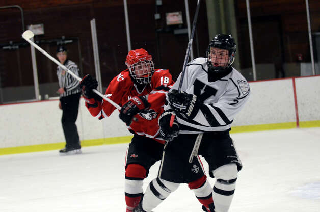 New Canaan's Peter Richardson (18) checks Xavier's Kade McCartin (7) during the boys hockey game at the Freeman Athletic Center in Middletown on Monday, Jan. 21, 2013. Photo: Amy Mortensen / Connecticut Post Freelance