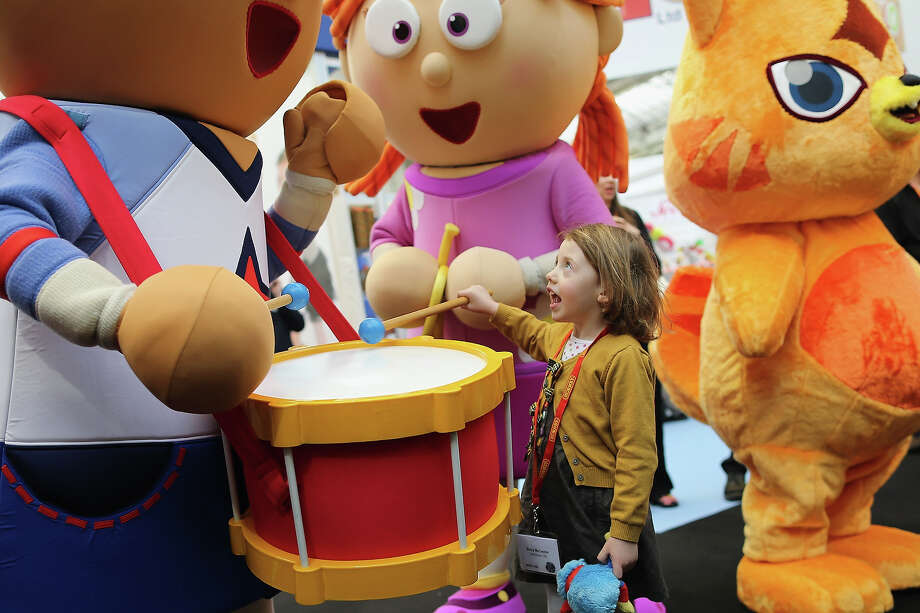 Betsy McCredie, 4, from Glasgow interacts with life size cartoon characters during the 2013 London Toy Fair at Olympia Exhibition Centre on January 22, 2013 in London, England. The annual fair which is organized by the British Toy and Hobby Association, brings together toy manufacturers and retailers from around the world. Photo: Dan Kitwood, Getty Images / 2013 Getty Images