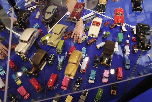 A woman arranges Oxford die cast model cars on a trade stand during the 2013 London Toy Fair at Olympia Exhibition Centre on January 22, 2013 in London, England. The annual fair which is organized by the British Toy and Hobby Association, brings together toy manufacturers and retailers from around the world. Photo: Dan Kitwood, Getty Images / 2013 Getty Images
