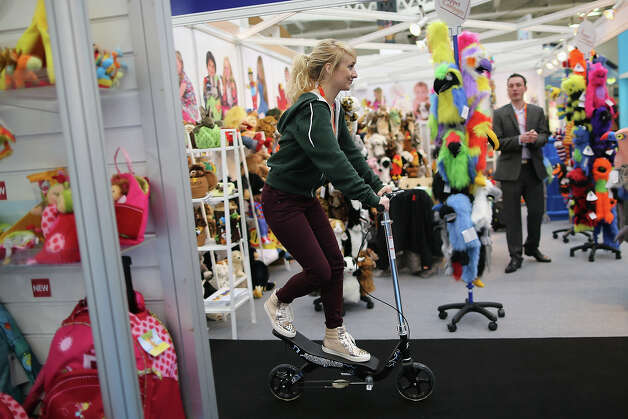 A woman rides a scooter through trade stands during the 2013 London Toy Fair at Olympia Exhibition Centre on January 22, 2013 in London, England. The annual fair which is organized by the British Toy and Hobby Association, brings together toy manufacturers and retailers from around the world. Photo: Dan Kitwood, Getty Images / 2013 Getty Images