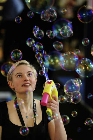 A woman on a trade stand blows bubbles during the 2013 London Toy Fair at Olympia Exhibition Centre on January 22, 2013 in London, England. The annual fair which is organized by the British Toy and Hobby Association, brings together toy manufacturers and retailers from around the world. Photo: Dan Kitwood, Getty Images / 2013 Getty Images