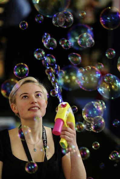 A woman on a trade stand blows bubbles during the 2013 London Toy Fair at Olympia Exhibition Centre