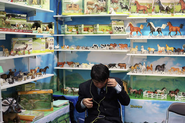 A man sits on a trade stand during the 2013 London Toy Fair at Olympia Exhibition Centre on January 22, 2013 in London, England. The annual fair which is organized by the British Toy and Hobby Association, brings together toy manufacturers and retailers from around the world. Photo: Dan Kitwood, Getty Images / 2013 Getty Images