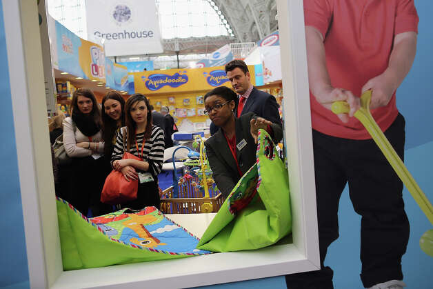 A woman shows clients items on a trade stand during the 2013 London Toy Fair at Olympia Exhibition Centre on January 22, 2013 in London, England. The annual fair which is organized by the British Toy and Hobby Association, brings together toy manufacturers and retailers from around the world. Photo: Dan Kitwood, Getty Images / 2013 Getty Images